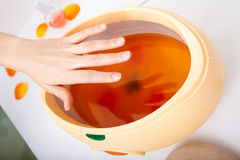 Female hand and orange paraffin wax bowl. Woman in beauty salon Stock Images