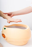 Female hand and orange paraffin wax bowl. Woman in beauty salon Royalty Free Stock Photo