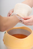 Female hand and orange paraffin wax bowl. Woman in beauty salon Royalty Free Stock Image