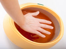 Female hand and orange paraffin wax bowl. Woman in beauty salon Stock Photography