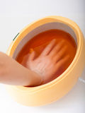 Female hand and orange paraffin wax bowl. Woman in beauty salon Royalty Free Stock Photography