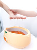 Female hand orange parrafin wax in bowl. Manicure beauty spa salon Stock Photography