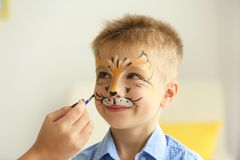 Female hand painting face of  boy. Female hand painting face of funny boy Royalty Free Stock Photography