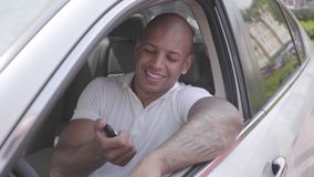 Female hand passes car keys to a smiling confident middle eastern man sitting in a vehicle. Female hand passes car keys to a smiling confident middle eastern stock footage