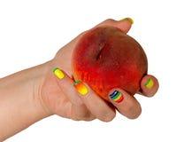 Female hand with a peach Stock Photos