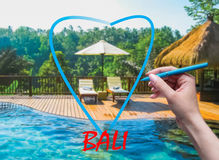 The female hand with pen drawing heart and Bali background. Abstract swimming pool and love to Bali concept royalty free stock images
