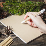 Female hand, pen, notebook, on the christmas decorations background Royalty Free Stock Photos