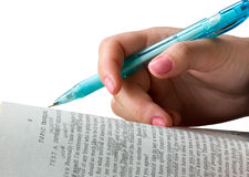 Female hand with a pencil. The female hand with a pencil lays on the opened book Stock Image
