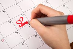 Female hand with pencil drawing heart and word love in calendar for Valentines day. Young female hand with pencil drawing hearts shape and words in calendar Stock Photos