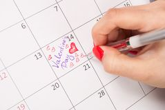 Female hand with pencil drawing hearts shape and words in calendar for Valentines day. Young female hand with pencil drawing hearts shape and words in calendar Stock Images