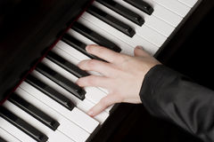 Female hand on a piano Stock Images