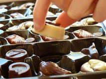 Female hand picking up chocolates Royalty Free Stock Photo