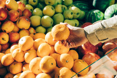 Female hand picks the oranges at the store Royalty Free Stock Images