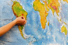Female hand pinning the big paper map by red pin Stock Images