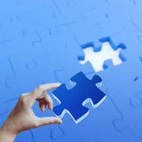 Female hand placing last piece of Puzzle Stock Image
