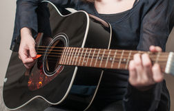 Female hand playing acoustic guitar Stock Images