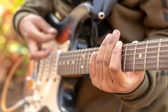 Female hand playing outdoor electric guitar royalty free stock photo