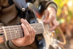 Female hand playing outdoor electric guitar stock photos