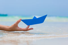 Female hand playing with paper boat in water on the beach. Female hand playing with paper boat in water on the white sand beach on blue sea background stock photos