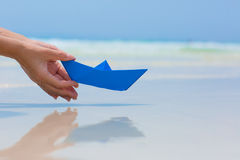 Female hand playing with paper boat in water on the beach. Female hand playing with paper boat in water on the white sand beach on blue sea background royalty free stock photos