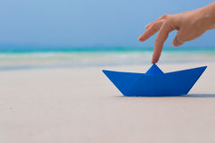 Female hand playing with paper boat in water on the beach. Female hand playing with paper boat in water on the white sand beach on blue sea background Stock Images