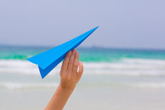 Female hand playing with paper plane on the beach. On blue sea background Royalty Free Stock Image