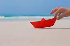 Female hand playing with red paper boat on the beach. Female hands playing with red paper boat on the white sand beach on blue sea background stock photos