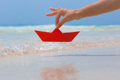 Female hand playing with red paper boat on the beach. Female hand playing with red paper boat in water on the white sand beach on blue sea background royalty free stock image