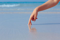 Female hand playing in the water on the beach. Female hand playing in the water on the white sand beach on blue sea background royalty free stock image