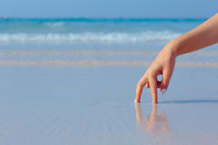Female hand playing in the water on the beach. Female hand playing in the water on the white sand beach on blue sea background Stock Photo