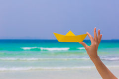 Female hand playing with yellow paper boat on the beach. Female hand playing with yellow paper boat in water on the white sand beach on blue sea background stock images