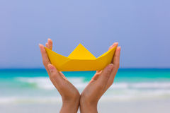 Female hand playing with yellow paper boat on the beach. Female hand playing with yellow paper boat on the white sand beach on blue sea background royalty free stock image