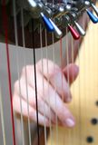 Female hand while plucking the strings of a harp 1 Royalty Free Stock Photo