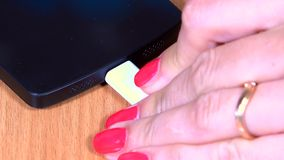 Female hand plug white micro usb cable to smart phone. Extreme closeup shot. 4K stock video footage