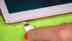 Female hand plug white micro usb cable to smart tablet computer stock footage