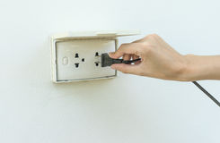 Female hand plugging in appliance to electrical outlet  Royalty Free Stock Photos