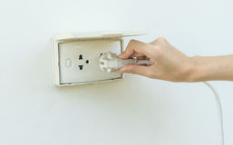 Female hand plugging in appliance to electrical outlet in wall o Stock Photography
