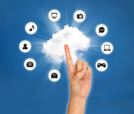 Female hand point on cloud with icon against blue sky Stock Image