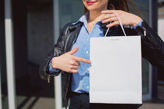 Female hand pointing at a blank and white shopping bag. Retail concept. Female hand pointing at a blank and white shopping bag. On paper bag space for text Stock Images