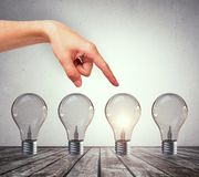 Choice, idea and success concept. Female hand pointing at creative row of illuminated light bulbs. Choice, idea and success concept stock photos