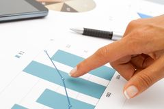 Female hand pointing at statistics. Close up of female hand using pointing at statistics Royalty Free Stock Images