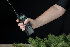 Female hand portable walkie talkies around the branches of the Christmas pine Royalty Free Stock Images