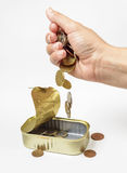Female hand pour down coins into fish can Royalty Free Stock Photography