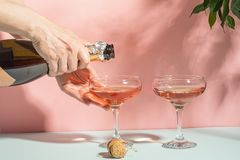Female hand pouring champagne or wine into glasses. Gentle pink background bright sunlight. Copy space minimalism. royalty free stock photo
