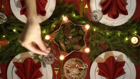Female hand is pouring confetti on the Christmas table. Festive red table setting with candles and garland. Top view. Slow motion stock video footage