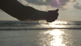 Female hand pouring sea sand through her fingers at sunset against an ocean background. Arm of young woman with sand stock video footage
