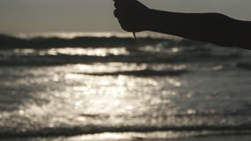 Female hand pouring sea sand through her fingers at sunset against an ocean background. Arm of young woman with sand stock video