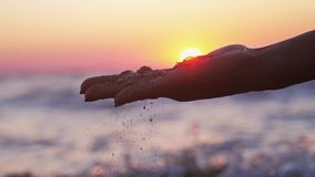 Female hand pouring sea sand through her fingers at sunset against the sea background. slow motion. 1920x1080 stock video footage