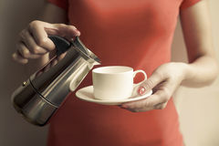 Female hand pours a drink into cup of the coffee maker. Royalty Free Stock Photos