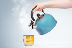 Female hand pours hot water from a blue kettle into a mug with a drink, on light background.  stock images